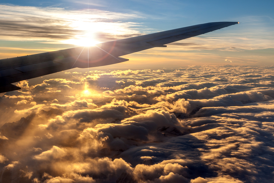 View of golden sunrise outside airplane window with deliberate lens flare over plane wing silhouette for effect. A sea of clouds over the Rocky Mountains underneath the plane.